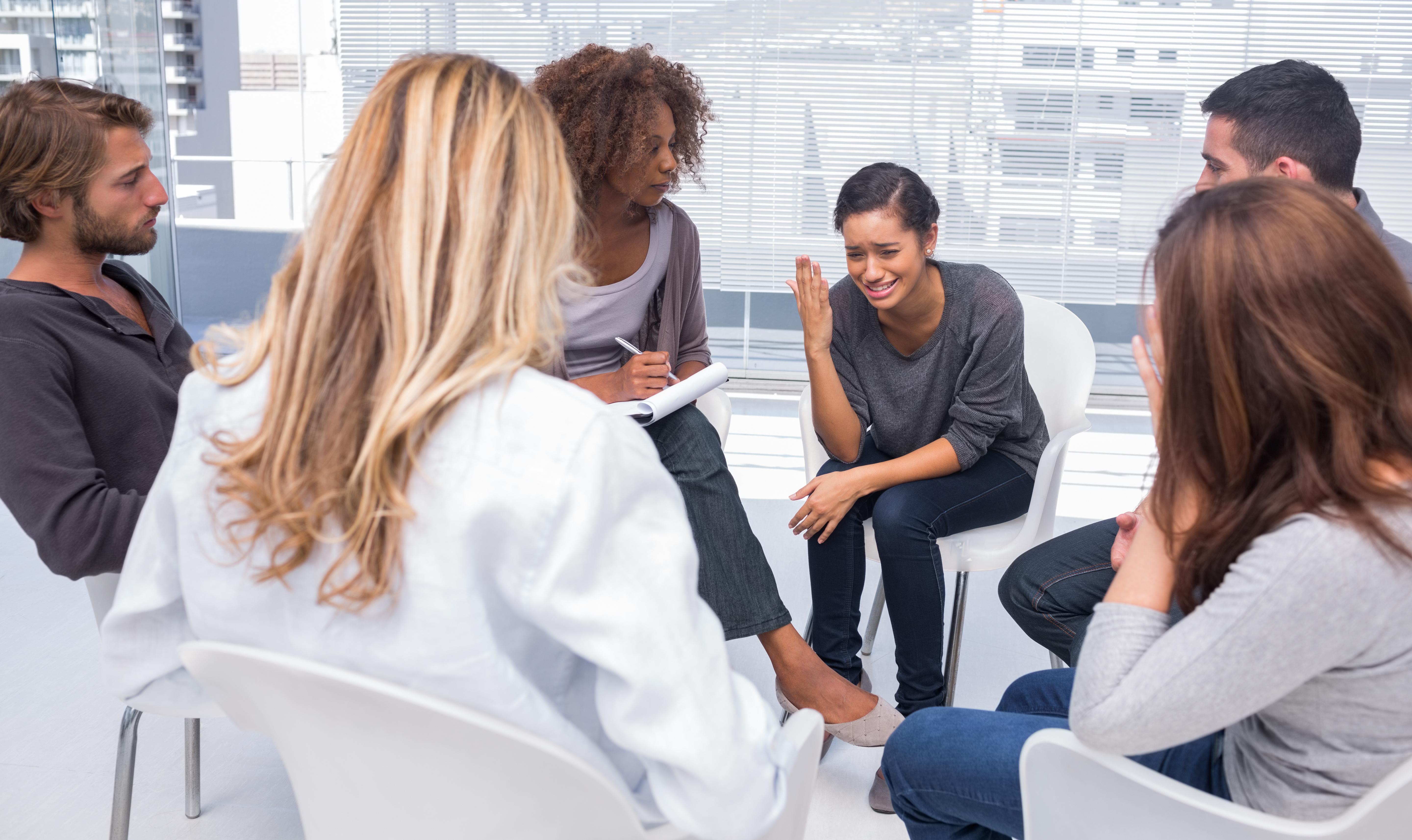 Woman sitting on chair and getting depressed in group therapy